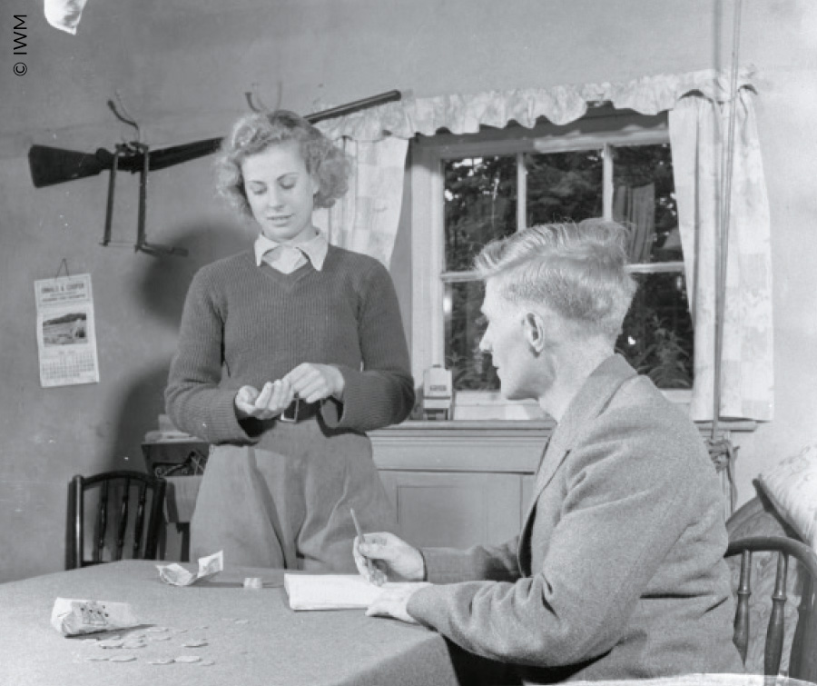 Landgirl Iris Joyce receives her first week's pay from the farmer with whom she is billited.