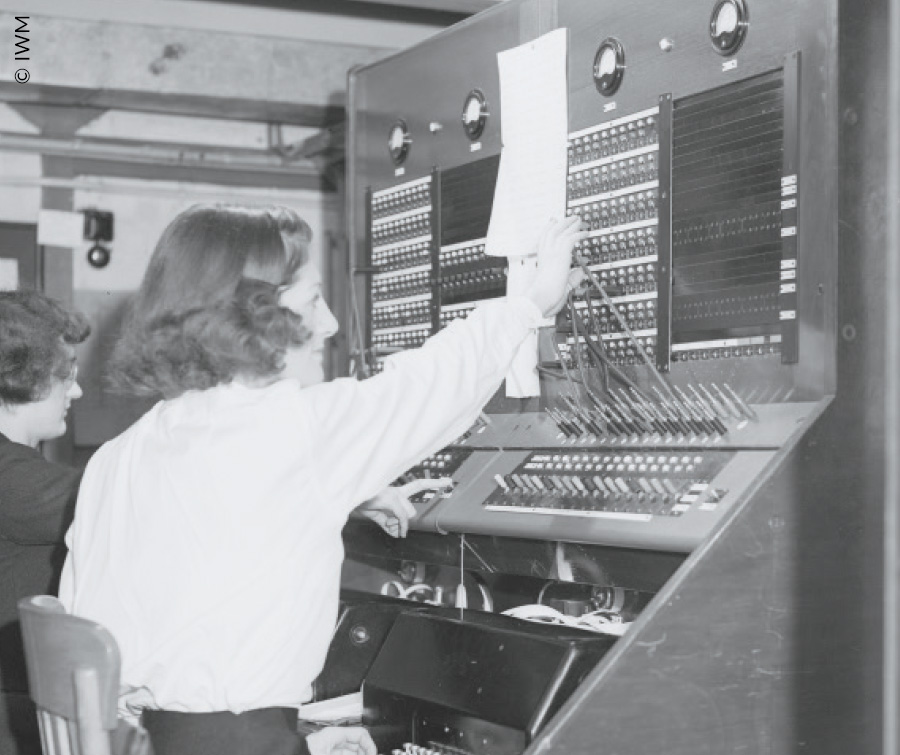 Operator using a switchboard to control the teleprinter machine.